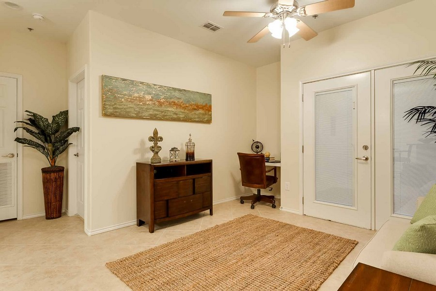 Apartment interior with area rug, desk nook, shelf against wall, and ceiling fan