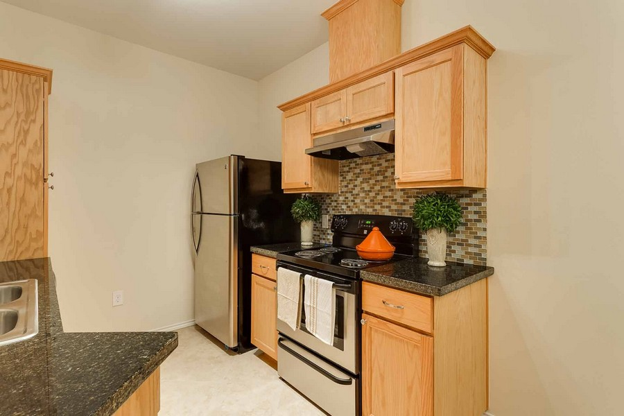 Apartment kitchen with silver appliances and granite countertops