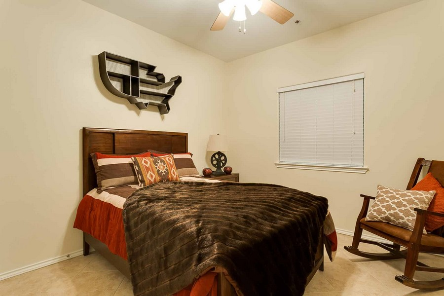 Apartment bedroom with ceiling fan and tile floor