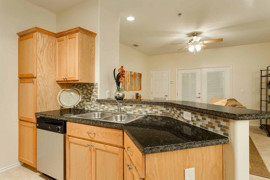 Kitchen area with granite countertops opening into living room