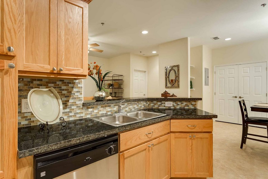 Kitchen sink with granite countertops, dishwasher, and cabinets