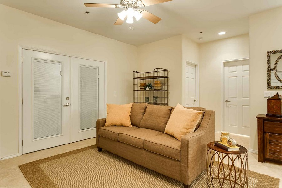 Couch in apartment living room with ceiling fan