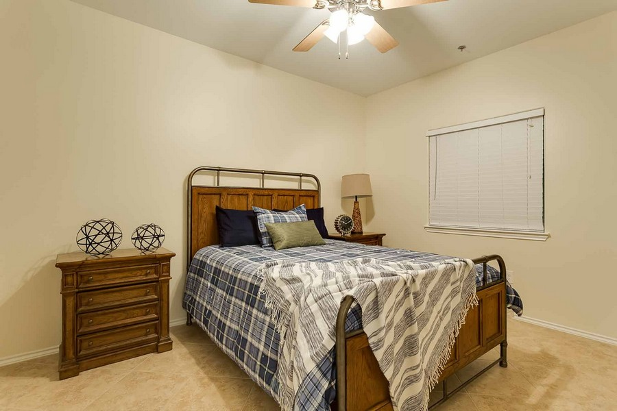 Bedroom with tile floor and bed with throw blanket on one corner