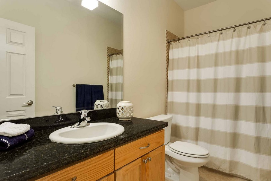 Bathroom showing sink with granite countertop and shower with striped curtain