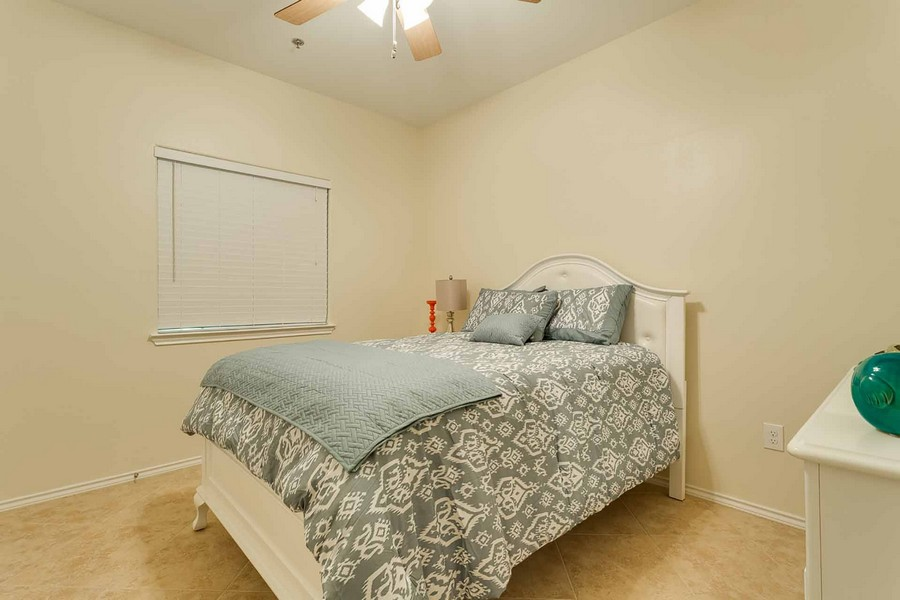 Second bedroom with tall white bed