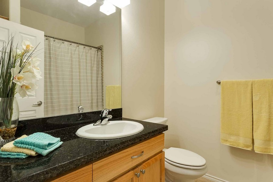 Bathroom sink with large mirror and granite countertop