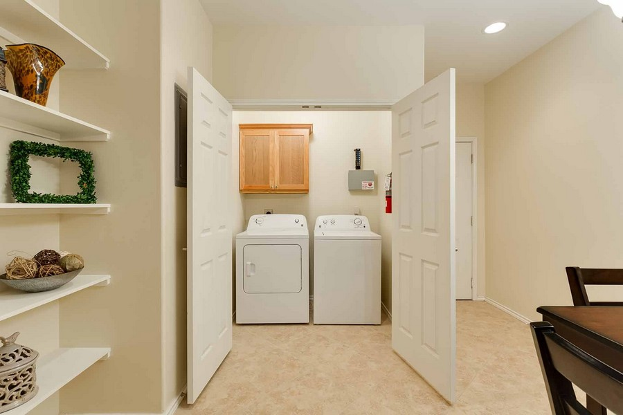 Doors near dining area opening to reveal laundry area