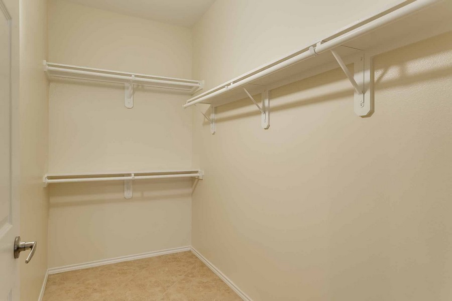 Large empty walk-in closet with shelves and racks for hangers
