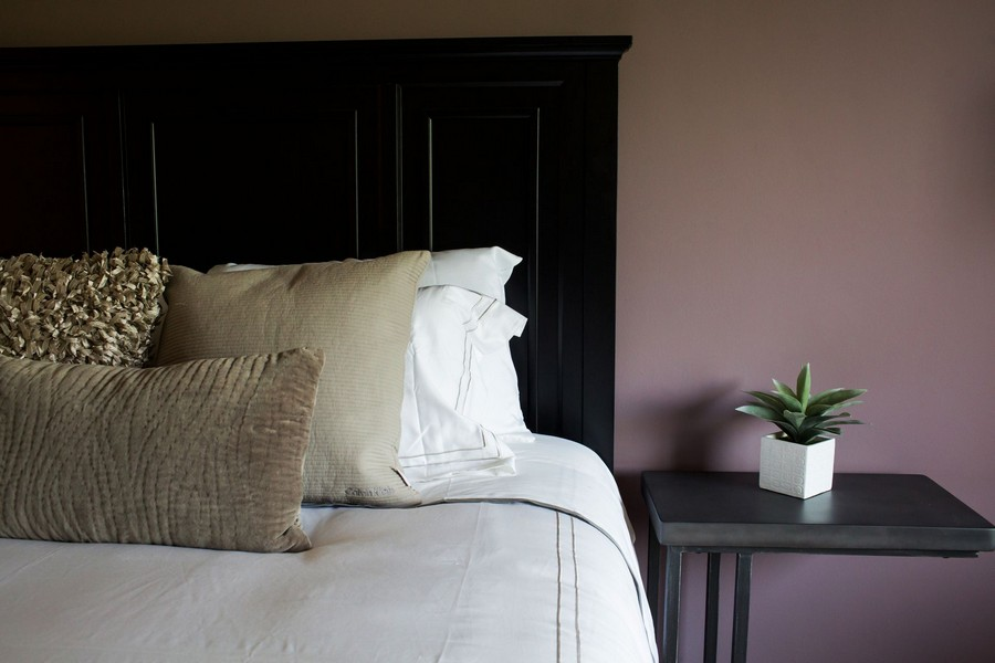 bedroom with black bed and side table, neutral bedding