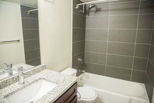 bedroom with counter, sink, toilet and shower with grey tile. Click to view the photo gallery.