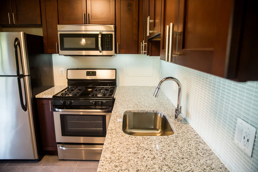 kitchen, with counters, sink, stainless steel appliances, dark wood cabinets