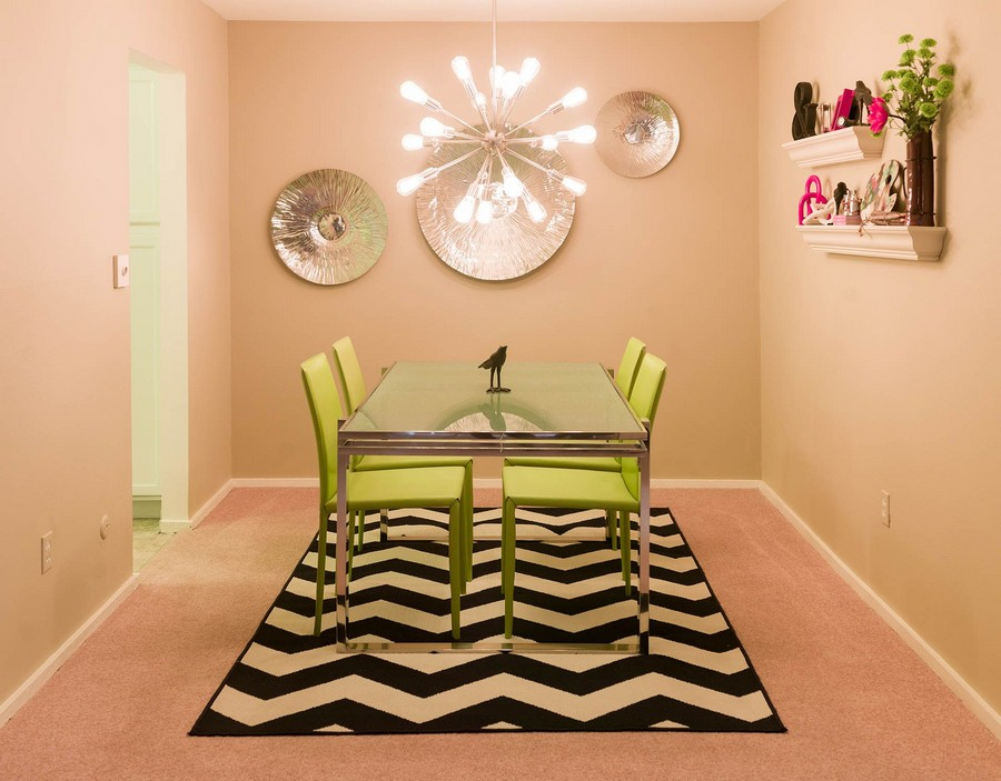 View of the apartment dining area with glass table, chairs and area rug.