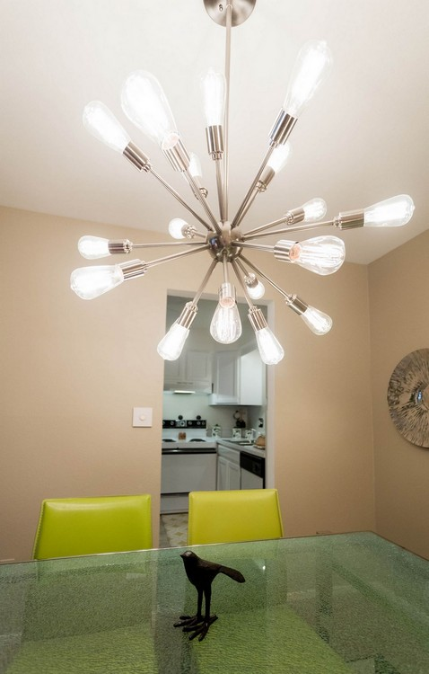 Chandelier above glass dining table