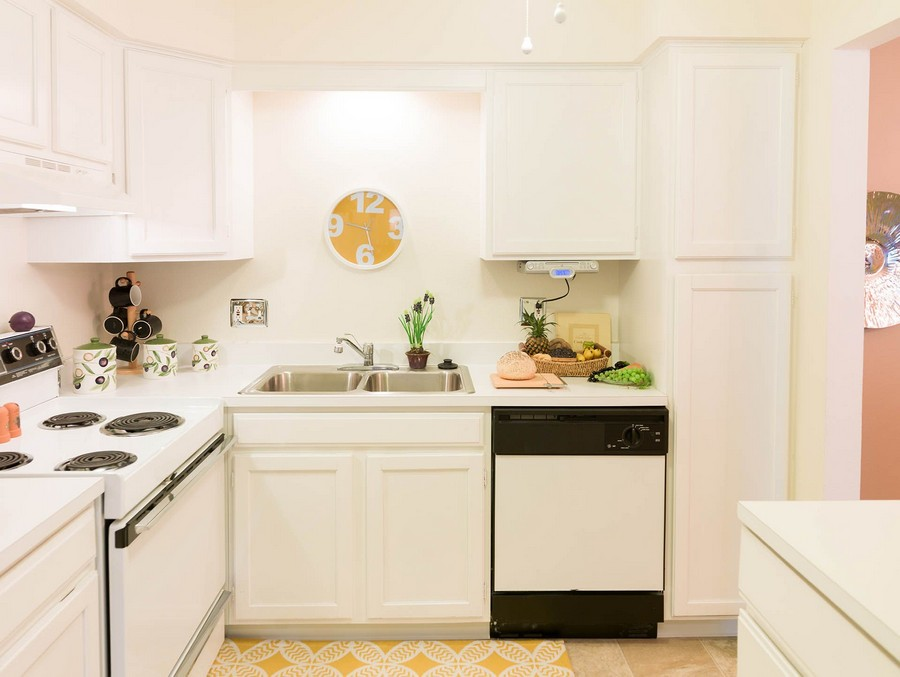View of apartment kitchen with white cabinets and a white dishwasher