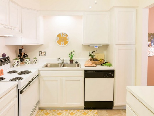 View of apartment kitchen with white cabinets and a white dishwasher. Click to view the photo gallery.