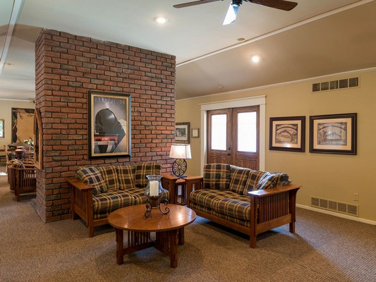 Apartment clubhouse with a seating area near a brick wall. Click to view the photo gallery.