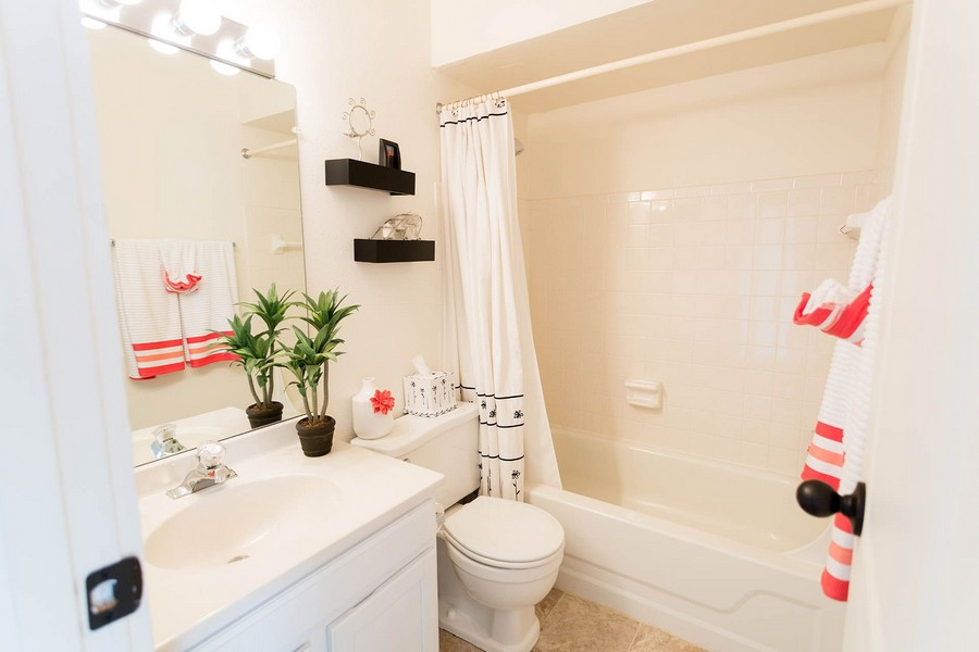 Apartment bathroom with white cabinets and ceramic bath tub