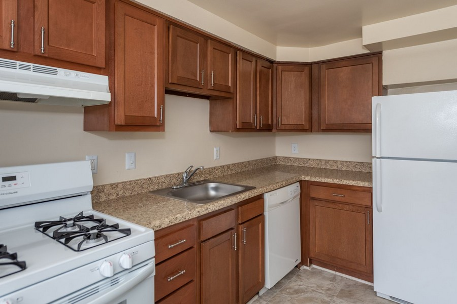 Kitchen with white appliances, wooden cabinets, sink