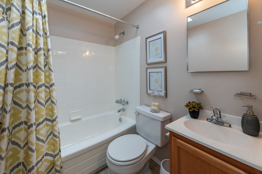 bathroom with shower curtain, pictures, toilet, sink