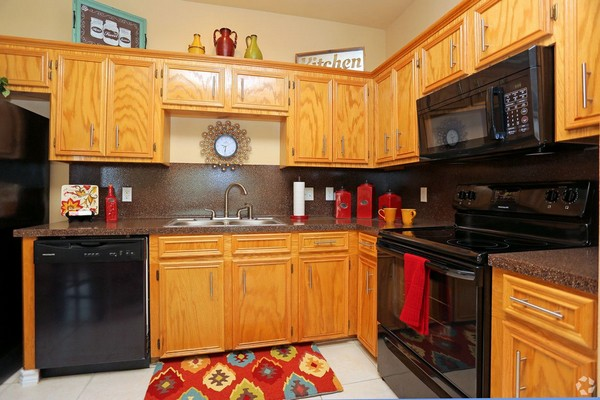 Apartment Kitchen with Black Appliances and Brown Cabinets. Click to view the photo gallery.