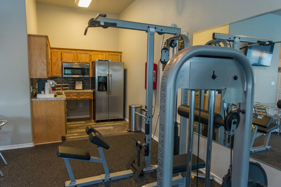 Fitness equipment and kitchen with brown cabinets.