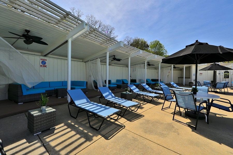 Tanning chairs and covered lounge area with outdoor fans and seating.