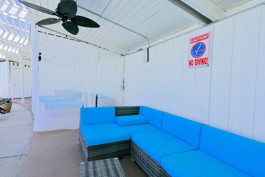 Covered outdoor seating area with fans and privacy curtains.