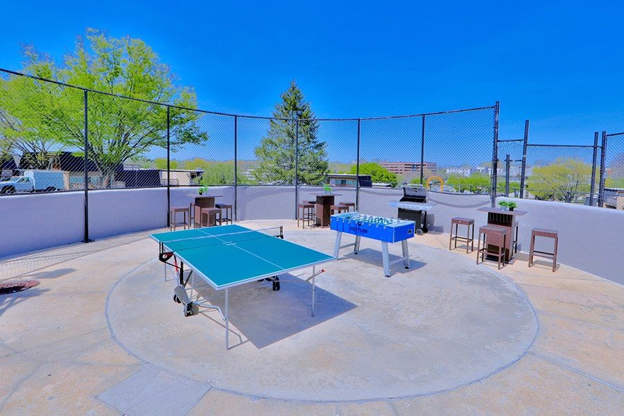 Outdoor grill area with ping pong and foosball tables.