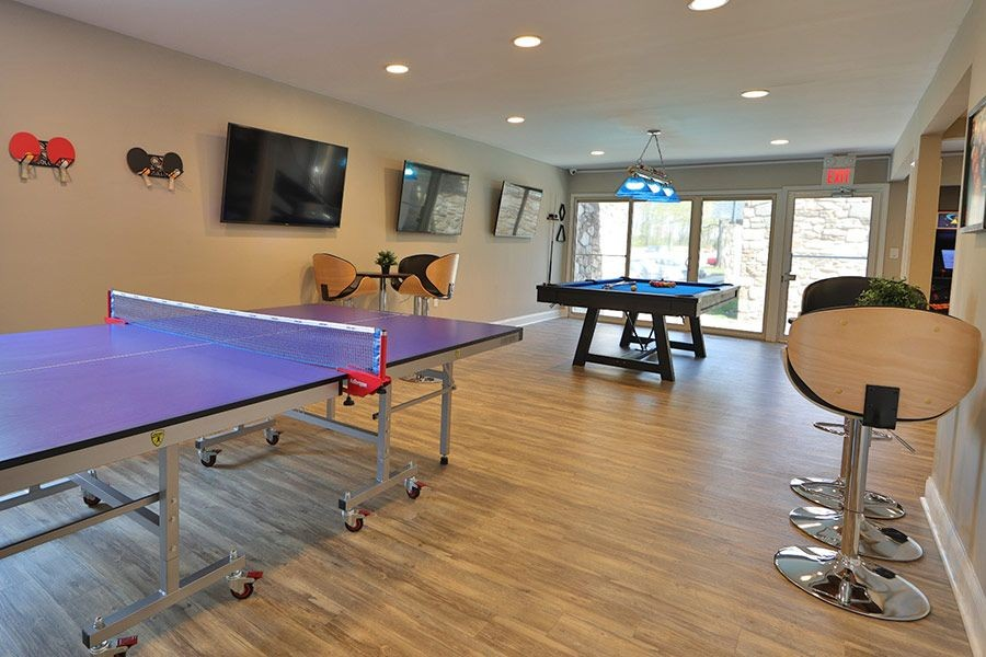 Community game room with ping pong, billiards, and televisions.