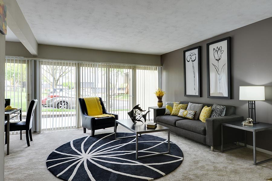 Living room area with large windows, furnished