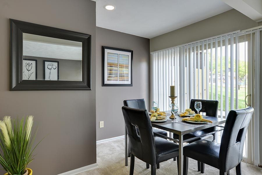 Dining area with table and chairs beside window, art on the walls