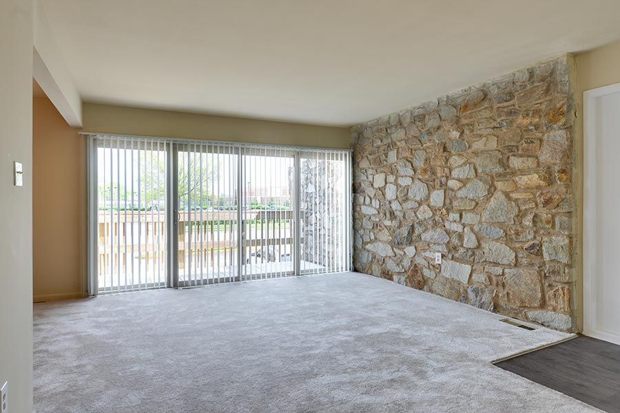 Living room with stone accent wall and windows