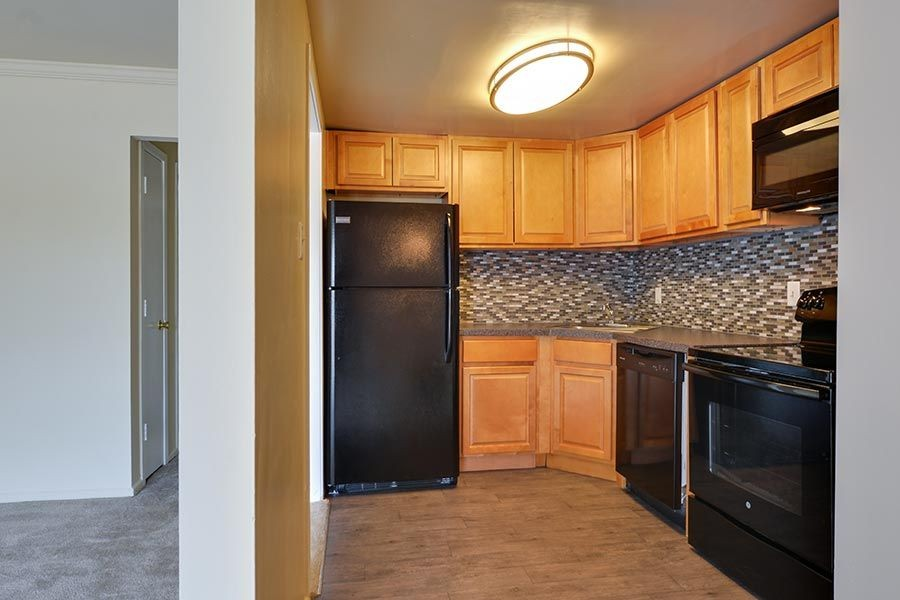 Kitchen area with black appliances and entryway