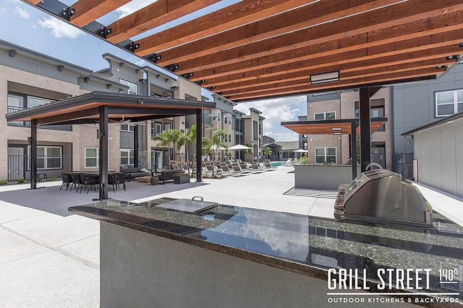 Outdoor grilling station, dining area, and poolside seating