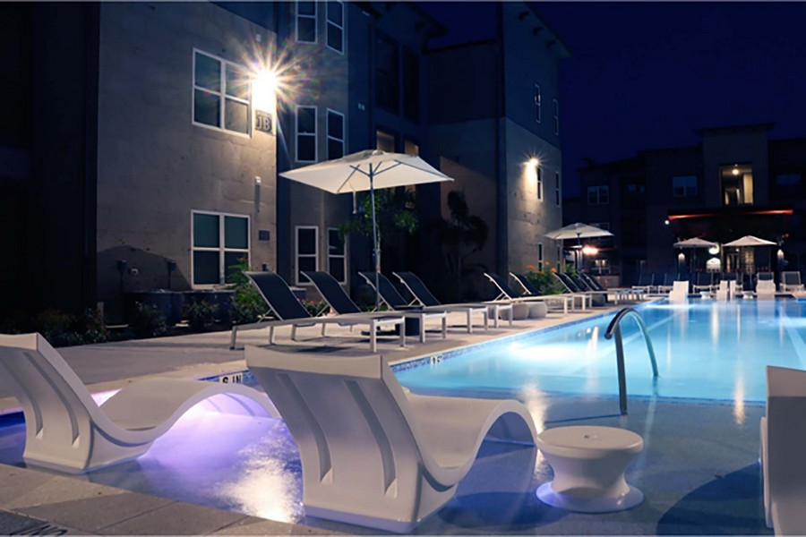 Night view of tanning ledge, swimming pool, and sun deck