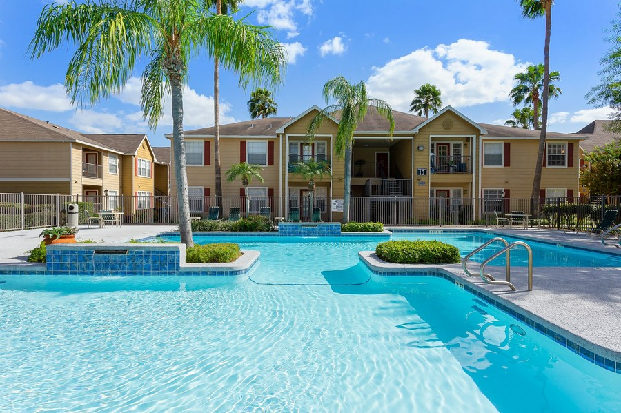 Sparkling swimming pool with landscaping in front of apartment buildings