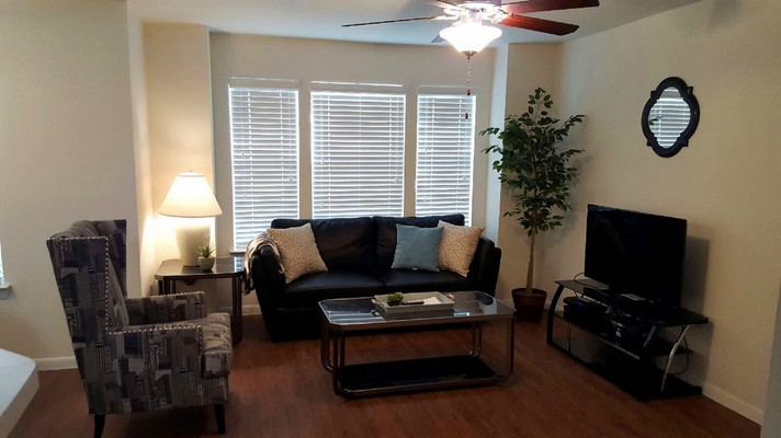Apartment living room with couches and large windows covered with blinds . Click to view the photo gallery.