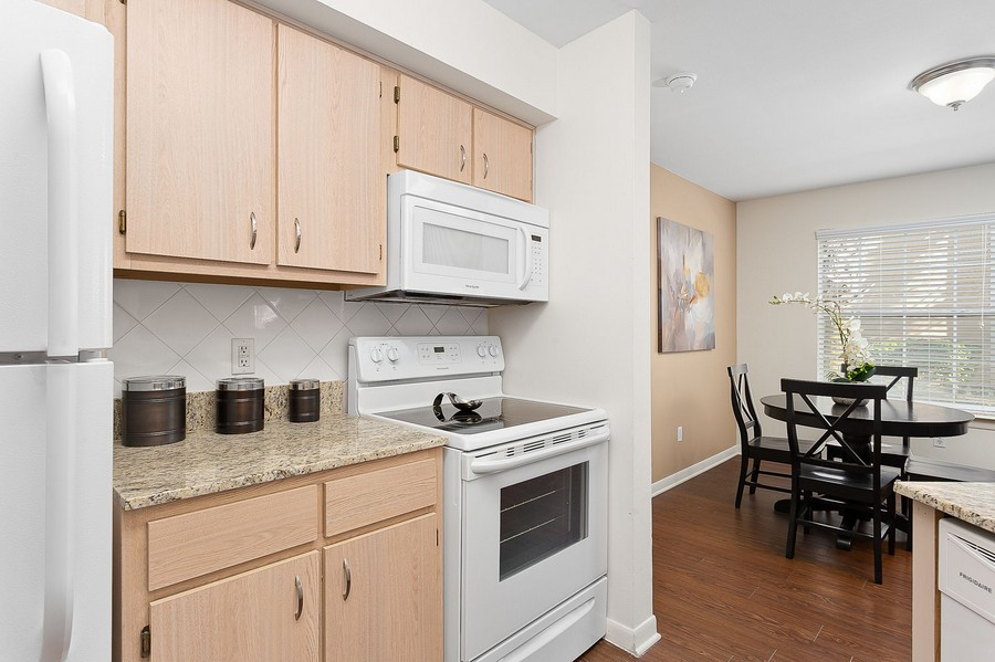 View of apartment kitchen and dining area with light fixtures.
