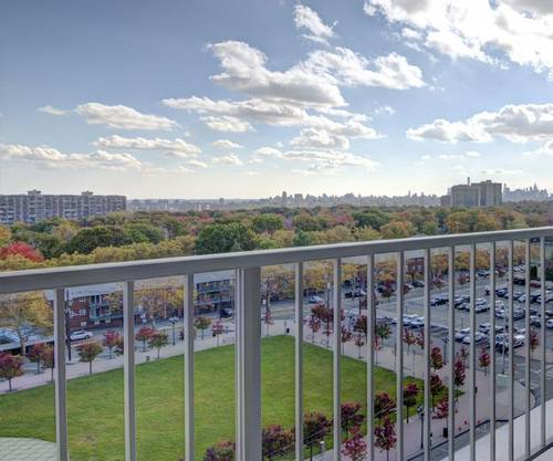view over railing to landscaped area and parking lot