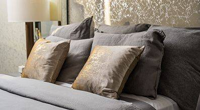 bed with gray and gold accent pillows with night stand nearby
