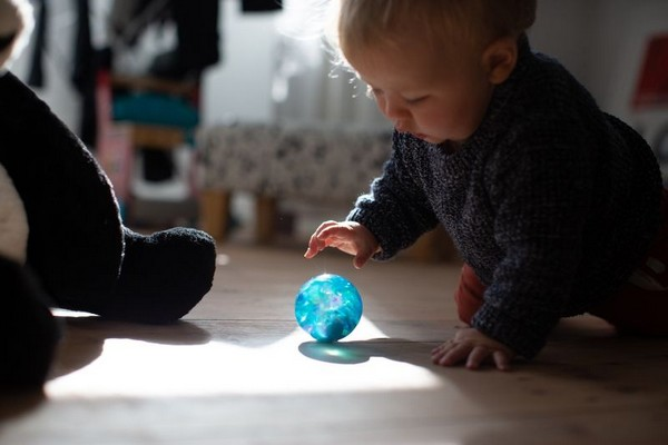 Infant with ball. Click to view the photo gallery.
