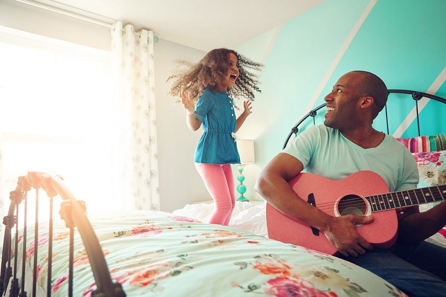 Dad playing guitar for daughter