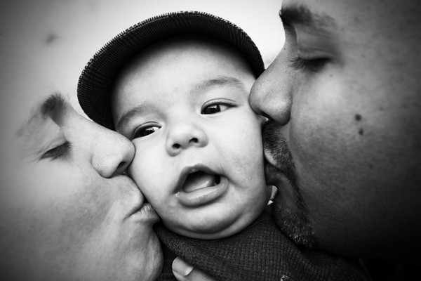 Man and woman kissing baby