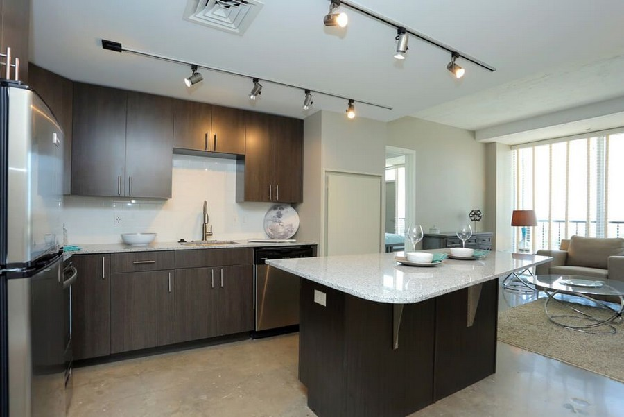 Living room and kitchen with island and stainless steel appliances