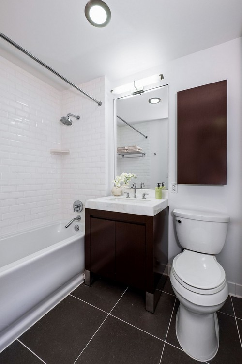 apartment bathroom that includes a deep tub with subway tile