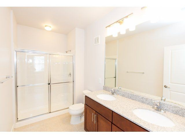 apartment bathroom with dual vanity and glass standing shower