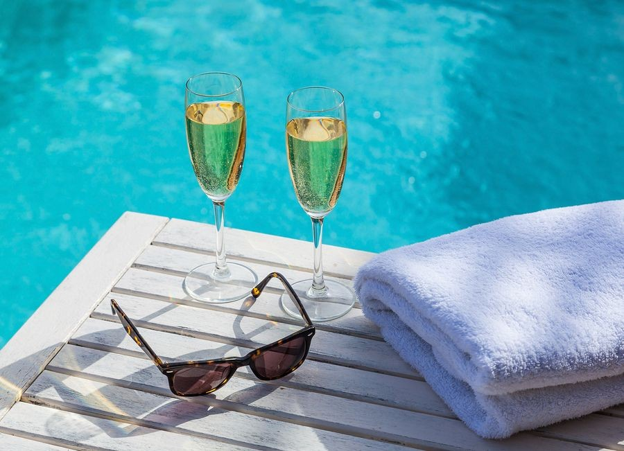 Drinks, sunglasses and a folded towel by the pool