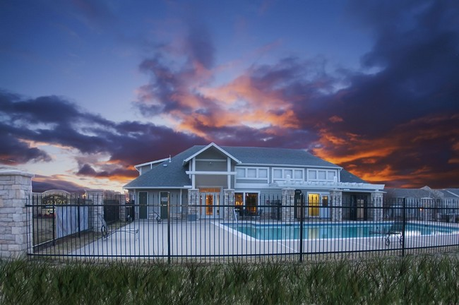 Exterior of clubhouse and pool with a beautiful evening sunset in the background.