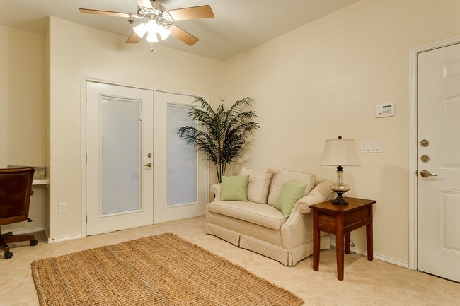 living room with ceiling fan, sofa, double doors, and alarm panel