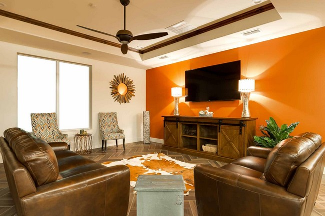 bright sitting area with large television and ceiling fan